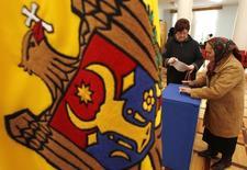 Люди голосуют на парламентских выборах в Кишиневе 28 ноября 2010 года. Две трети депутатов покинули фракцию Компартии в парламенте Молдавии, дав Демократической партии шанс собрать новую коалицию и добиться выдвижения в премьеры непопулярного магната Владимира Плахотнюка, в понедельник объявившего о возвращении в политику. REUTERS/Gleb Garanich