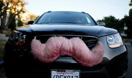 A driver with the ride-sharing service Lyft waits for a customer on a street in Santa Monica, California October 17, 2013.  REUTERS/Lucy Nicholson