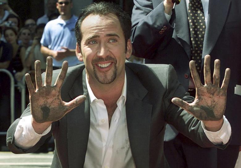 Actor Nicholas Cage smiles after placing his handprints in the forecourt at Grauman's Chinese Theater in Hollywood in this file photo taken August 14, 2001. REUTERS/Fred Prouser/Files