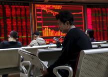 Una persona lee un diario en una correduría en Pekín, dic 17, 2015. Los inversores globales redujeron sus posiciones en acciones y las aumentaron en bonos, según un sondeo de Reuters a gestores de fondos publicado el martes, por el temor a una desaceleración económica mundial y porque persiste la incertidumbre sobre el ritmo de endurecimiento monetario de la Fed.  REUTERS/Kim Kyung-Hoon
