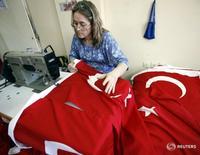 Женщина шьет турецкие флаги в Измире 11 мая 2007 года. Рост ВВП Турции в 2015 году может превысить ожидания и составить 3,5-4 процента, а в 2016 году - оказаться выше официального прогноза в 4 процента, незначительно отреагировав на экономические санкции, введенные против Анкары разгневанной Москвой, сказал в интервью Рейтер вице-премьер Турции Мехмет Шимшек. REUTERS/Fatih Saribas