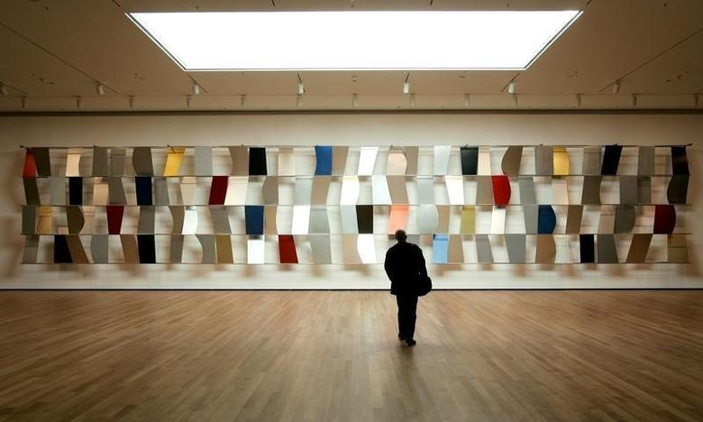 A visitor walks towards Ellsworth Kelly's ''Sculpture For a Large Wall'' of anodized aluminum (1957) in the newly renovated Museum of Modern Art in New York City, November 15, 2004.