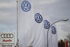 El logo de Audi cerca de unas banderas con el logo de Volkswagen, en una automotora en Bad Honnef, Alemania, 4 de noviembre de 2015. Audi, la marca insignia de Volkswagen, ajustó el lunes su plan de gastos para 2016 y retrasó la construcción de un nuevo túnel de aire por el escándalo sobre la manipulación de las pruebas de emisiones del fabricante de automóviles alemán.  REUTERS/Wolfgang Rattay