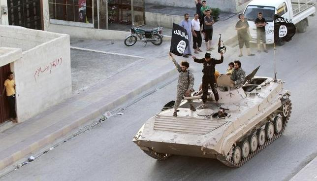 Militant Islamist fighters hold the flag of Islamic State (IS) while taking part in a military parade along the streets of northern Raqqa province in this June 30, 2014 file photo. REUTERS/Stringer/Files