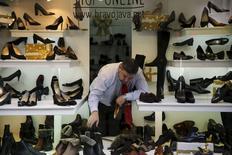 Las ventas minoristas ralentizaron su ritmo de crecimiento en noviembre, tras un mes previo de subidas récord, encadenando el decimosexto mes de alzas, apoyadas en un mayor consumo de los hogares. En la imagen, un dependiente coloca zapatos en un escaparate en Madrid, el 21 de diciembre de 2015.  REUTERS/Marcelo del Pozo