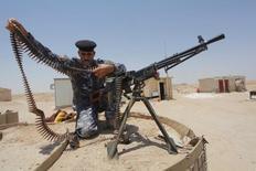 """Боец сил безопасности Ирака заправляет патронную ленту в пулемет в пустыне к югу от Багдада 28 июня 2014 года. Премьер-министр Ирака Хайдер аль-Абади заявил, что иракские военные, добившиеся первой крупной победы за полтора года, разгромят боевиков """"Исламского государства"""" в 2016 году.  REUTERS/Alaa Al-Marjani"""