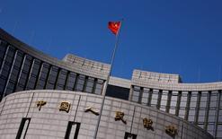 Una bandera china ondea afuera de la sede del Banco Central de China, en Pekín, 3 de abril de 2014. El banco central de China dijo el martes que aplicará un nuevo sistema para evaluar los riesgos macro-prudenciales en el mercado financiero en 2016 a medida que los activos bancarios del país se diversifican cada vez más. REUTERS/Petar Kujundzic