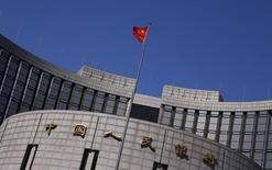 Una bandera nacional china ondea afuera de la sede del Banco Central, en Pekín, 3 de abril de 2014. El banco central de China suspendió temporalmente algunas operaciones de cambio de divisas de varios bancos extranjeros hasta fines de marzo, dijeron el miércoles a Reuters tres fuentes con conocimiento directo de la situación. REUTERS/Petar Kujundzic