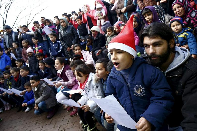 Migrants sing the traditional German christmas carol ''Oh christams tree'' during a Christmas gathering, organized by local relief organization ''Die Johanniter'', with christmas presents for the children at the refugee camp in Hanau, Germany, December 24, 2015.  REUTERS/Kai Pfaffenbach