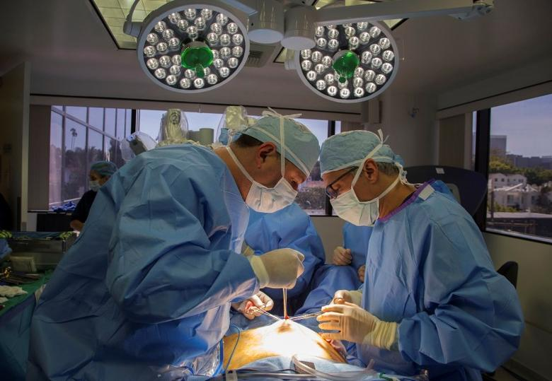Doctors David Ghozland and Marc Winter make an incision in the belly button of a 49-year-old woman, Sheryl, who had two fibroids, in preparation for a single-site robotic-assisted hysterectomy at miVIP Surgery Center, in Los Angeles, California April 23, 2014. REUTERS/Lucy Nicholson