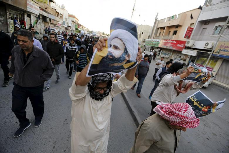 Protesters holding poster of Saudi Shi'ite cleric Nimr al-Nimr protest against his execution by Saudi authorities in the village of Sanabis, west of Manama, Bahrain January 3, 2016. REUTERS/Hamad I Mohammed