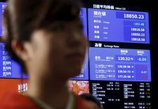 El índice Nikkei se ve detrás de una mujer que participa en la ceremonia de apertura de la Bolsa de Tokio, en Tokio, Japón, 4 de enero de 2016. Las acciones japonesas cayeron el martes por segundo día consecutivo y en una sesión volátil a un nuevo mínimo en dos meses y medio después de que los títulos chinos volvieron a operar en territorio negativo, lo que limitó el apetito de los inversores. REUTERS/Yuya Shino