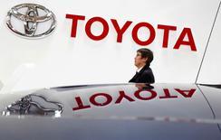 Una persona camina bajo el logo de Toyota, en la sala de exhibición de la compañía en Tokio, 4 de febrero de 2015. Toyota Motor Corp y sus socios en un emprendimiento conjunto pretenden vender 1,15 millones de vehículos en China este año, incumpliendo expectativas generales para el mayor mercado automotor del mundo. REUTERS/Yuya Shino