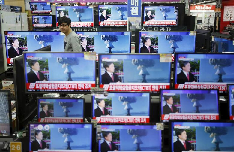 A sales assistant watches TV sets broadcasting a news report on North Korea's nuclear test, in Seoul, January 6, 2016. REUTERS/Kim Hong-Ji