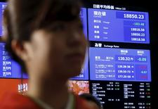 El índice Nikkei se ve detrás de una mujer que participa en la ceremonia de apertura de la Bolsa de Tokio, en Tokio, Japón, 4 de enero de 2016. Las acciones de Japón cayeron el miércoles después de que un sondeo privado aumentó las preocupaciones de que la economía china esté perdiendo impulso, mientras que el anuncio de una prueba de una bomba de hidrógeno por parte de Corea del Norte introdujo nueva incertidumbre geopolítica y redujo el apetito por el riesgo. REUTERS/Yuya Shino