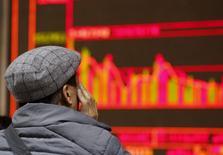 Un hombre mira un tablero electrónico que muestra la información de las acciones, en una correduría en Pekín, China, 6 de enero de 2016. Los principales índices bursátiles de China abrieron la sesión del miércoles con ganancias, luego de que medios estatales reportaron que el bloqueo a las ventas de papeles de grandes accionistas seguirá vigente hasta que se promulguen nuevas normas de administración del proceso. REUTERS/Kim Kyung-Hoon