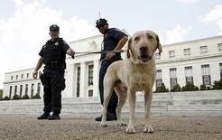 Police officers stand with their dog outside the Federal Reserve patrol in front  of the building with their dog Brodie in Washington September 1,  2015.  REUTERS/Kevin Lamarque