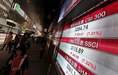 Personas caminan junto a unas pantallas que muestran los índices de mercados chinos, en Hong Kong, China, el 7 de enero de 2016. China aceleró el jueves una devaluación del yuan, provocando que las monedas de la región asiática tambalearan y los mercados bursátiles se hundieran, porque los inversores ahora temen que el gigante oriental esté comenzando una guerra comercial contra sus competidores. REUTERS/Bobby Yip