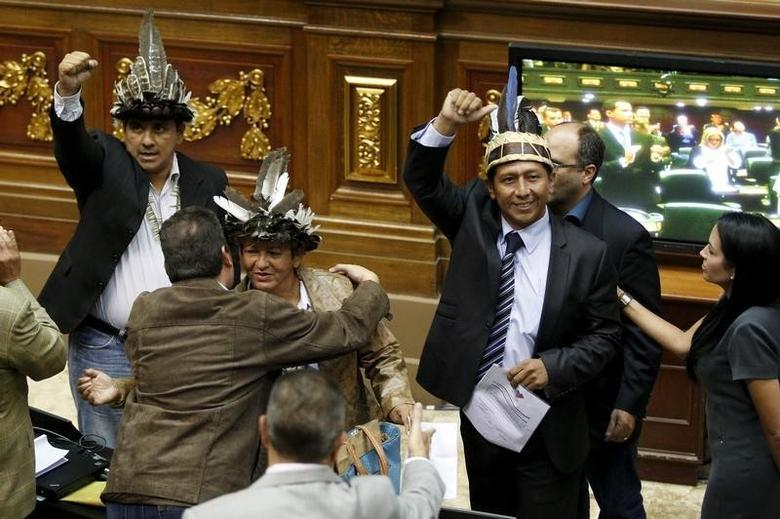 Julio Ygarza (L), Nirma Guarulla (C) and Romel Guzamana (2nd R), deputies of Venezuelan coalition of opposition parties (MUD), celebrate after their swearing-in ceremony during a session of the National Assembly in Caracas January 6, 2016. REUTERS/Marco Bello