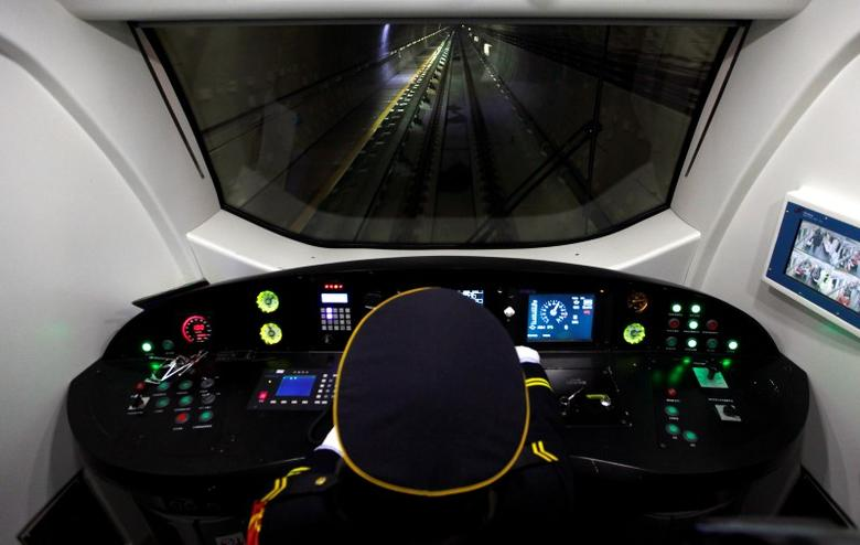 A train driver drives a train through a section of a new subway line during an official opening in Beijing December 30, 2010. REUTERS/David Gray
