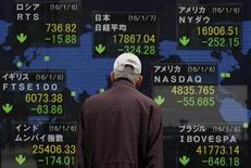 Un peatón observa un panel que muestra las cotizaciones de las bolsas de varios países, en Tokio, 7 de enero de  2016. Las acciones japonesas cayeron el viernes, marcando el primer inicio del año desde 1949 en que registró cinco bajas consecutivas diarias. REUTERS/Yuya Shino