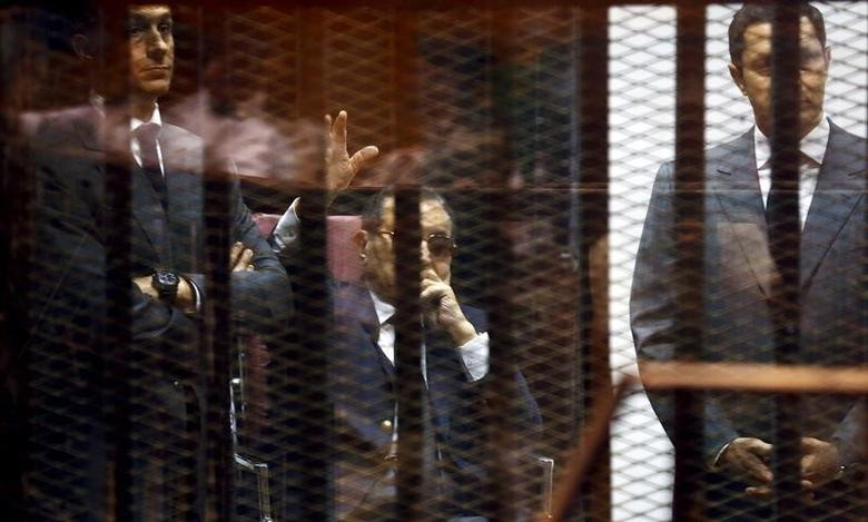 Egypt's former president Hosni Mubarak waves to his supporters with his sons Gamal (L) and Alaa (R) inside a cage in a courtroom during them trial at the police academy, on the outskirts of Cairo, in this May 9, 2015. filem photo.REUTERS/Amr Abdallah Dalsh