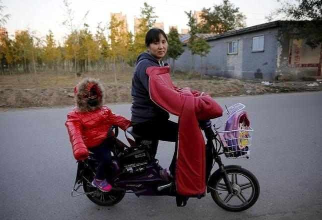 Lv Hongli and her second daughter ride on a bicycle while posing at a migrant workers' village in Beijing, China October 30, 2015. REUTERS/Kim Kyung-Hoon