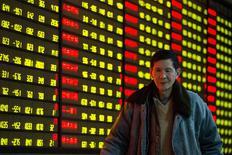 """Un inversor pasa junto a una pantalla electrónica con información bursátil en una correduría en Nanjing, en la provincia china de Jiangsu, el 11 de enero de 2016. El yuan, la moneda de China, volvía a dominar los movimientos de los principales mercados cambiarios el lunes, con un alza de 1 por ciento contra el dólar en las transacciones """"offshore"""" después de reportes que indicaron otra agresiva intervención de parte de Pekín. REUTERS/China Daily"""