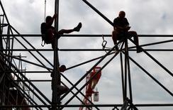 Trabajadores de la construcción, fotografiados durante las tareas en un edificio en el centro de Múnich, 15 de julio de 2013. Las condiciones económicas se están estabilizando en China y el panorama es de un crecimiento sostenido en la zona euro, mientras que las economías de Estados Unidos y Gran Bretaña están perdiendo impulso, dijo el lunes la Organización para la Cooperación y el Desarrollo Económico (OCDE). REUTERS/Michaela Rehle