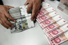 Funcionário conta notas de dólar e iuan em agência do Banco da China em Taiyuan. 04/01/2016 REUTERS/Jon Woo