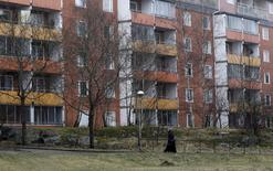 A woman walks past a housing block in the Husby suburb of Stockholm, Sweden, in this April 7, 2014 file picture.  REUTERS/Ints Kalnins/Files