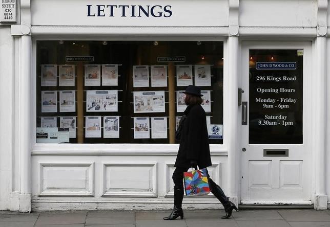 A woman walks past an estate agent in Chelsea, London February 7, 2013.   REUTERS/Stefan Wermuth