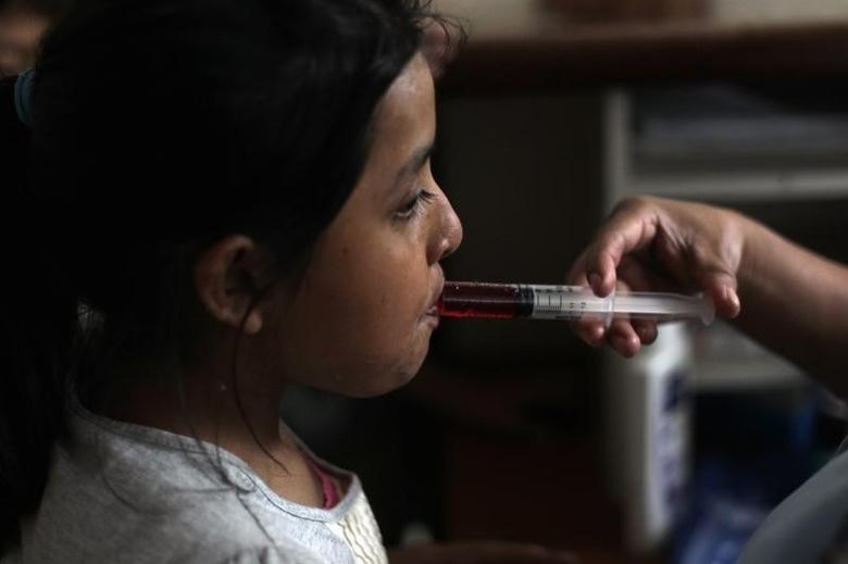 A nurse uses a syringe to give liquid medicine to a girl at San Jose Hospice in Sacatepequez, about 45 km (27 miles) of Guatemala City, November 30, 2011. REUTERS/Jorge Dan Lopez/Files