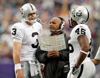 Oakland Raiders head coach Hue Jackson (R) looks at a play chart with Raiders quarterback Carson Palmer (3) and fullback Marcel Reece (45) during a timeout in the first half of their NFL football game against the MInnesota Vikings in Minneapolis, November 20, 2011.  REUTERS/Eric Miller