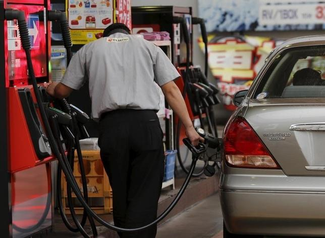 A gas station worker fuels a vehicle in Tokyo August 26, 2015. Crude oil futures edged up on Wednesday, but were still not far off 6-1/2 year lows after China's central bank moved to support the country's stumbling economy, while concerns about a supply glut capped gains.  REUTERS/Toru Hanai  - RTX1PP3C