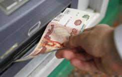 Мужчина забирает рублевую купюру из банкомата в Москве 2 сентября 2014 года. Российская валюта утром четверга ушла в плюс перед налоговым периодом на фоне низкого реального спроса на валюту и высокой вероятности секвестра бюджета РФ, невзирая на дешевую нефть. REUTERS/Maxim Zmeyev