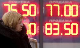 Женщина проходит мимо вывески с курсами валют в Москве 12 января 2016 года. Рубль в четверг показывает в основном положительную динамику перед налоговым периодом на фоне низкого реального спроса на валюту, профицита текущего счета РФ и высокой вероятности секвестра российского бюджета - факторов, компенсирующих пока негативный эффект от дешевой нефти. REUTERS/Sergei Karpukhin