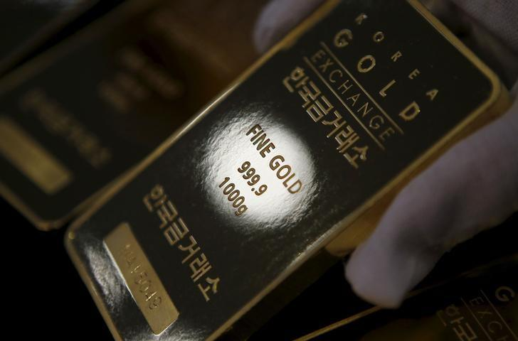 An employee poses for photographs with one kilogram gold bars at the Korea Gold Exchange in Seoul, South Korea, July 31, 2015.  REUTERS/Kim Hong-Ji