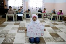 Syrian refugee Islem Halife, 11, shows a drawing of her home in Syria, as she sits in a classroom where she learns the Quran in Nizip refugee camp in Gaziantep province, Turkey, December 13, 2015.  REUTERS/Umit Bektas