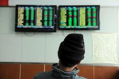 Un inversor mira unas pantallas que muestran información bursátil, en una correduría en Qingdao, provincia de Shandong, China, 11 de enero de 2016. El yuan de China cayó el jueves a pesar de los esfuerzos de las autoridades, debido a que el pesimismo en los mercados globales contrarrestó las señales de que la economía de China no se estaría debilitando tan rápido como algunos inversores temían. REUTERS/China Daily