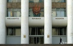 Человек проходит мимо здания парламента Модавии в Кишиневе 7 марта 2005 года. Парламентское большинство и президент Молдавии нашли компромиссную кандидатуру будущего премьера после трех месяцев противостояния, чем отвели угрозу досрочных выборов и дали надежду на выход из затяжного политического кризиса. REUTERS/Bogdan Cristel
