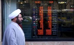 A cleric walks past a currency exchange shop in Tehran's business district, Iran, January 17, 2016. REUTERS/Raheb Homavandi/TIMA