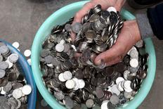 El banco central de China prepara un aumento del coeficiente de reservas requerido para los depósitos en yuanes en bancos de compensación a partir del 25 de enero, en el más reciente intento de frenar la especulación con la divisa china, dijeron tres fuentes que han visto el documento que detalla el cambio. En la foro, un himbre sumerge las manos en una colección de monedas de 1 yuan en Zhengzhou, China, el 11 de enero 2016.  REUTERS/Stringer