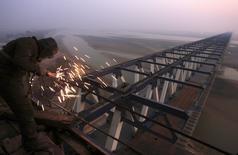Foto de archivo de un trabajador soldando una estructura de metal en el sitio de la construcción de los rieles de un puente, en Zhengzhou, provincia de Henan, China. 17 de diciembre de 2009. La economía china enfrenta crecientes presiones a la baja, pero los fundamentos económicos siguen siendo sólidos, informó la agencia estatal de noticias Xinhua citando declaraciones dadas el lunes por dos líderes del país. REUTERS/Donald Chan/Files