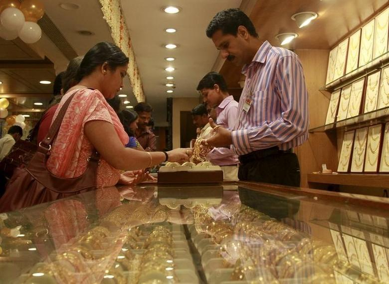 A woman checks gold bangles inside a jewelry showroom on the occasion of Akshaya Tritiya, a major gold buying festival, in Kochi April 21, 2015. REUTERS/Sivaram V/Files