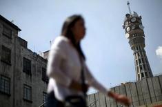 Una mujer pasa frente a una antena de telecomunicaciones en Ciudad de México, oct 8, 2015. La firma mexicana de telecomunicaciones Axtel dijo el lunes que sus accionistas aprobaron su fusión con la telefónica local Alestra a partir del 15 de febrero y la contratación de un crédito por 750 millones de dólares que usará para pagar tres emisiones de bonos de deuda.  REUTERS/Edgard Garrido