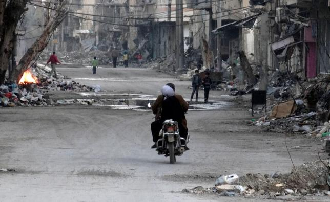 File pic of a man and a woman riding a motorcycle along a street filled with debris of damaged buildings in Deir al-Zor March 5, 2014. REUTERS/Stringer