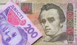 Банкноты валюты гривна в Киеве 6 августа 2014 года. Нацбанк Украины увеличил предложение на валютном аукционе в поддержку гривны во вторник более чем вдвое до $50 миллионов на фоне падения гривны ниже 10-месячного минимума. REUTERS/Konstantin Chernichkin
