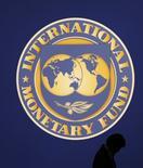 Homem passa por logo do FMI em Tóquio. 10/10/2012 REUTERS/Kim Kyung-Hoon
