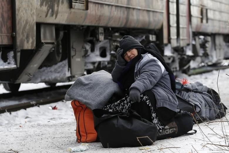 A migrant sits on her bags while waiting for a train to depart to Croatia at train station in Presevo, Serbia, January 19, 2016. REUTERS/Marko Djurica